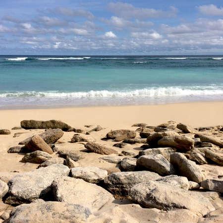 Tropical beach, ocean waves, sand and stones, sky and clouds, seascape Zdjęcie Seryjne