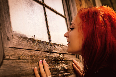 woman cuusly looks in window of old thrown house Stock Photo - 26880241