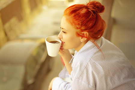 good morning womans with cup of fragrant coffee on balcony photo