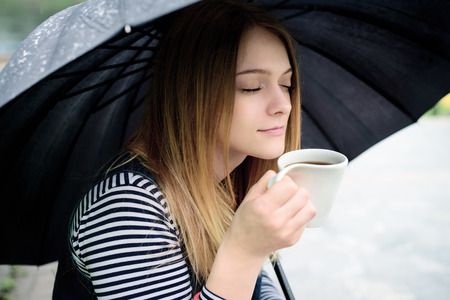 womanl drinks fragrant coffee with pleasure under umbrella in bad weather photo