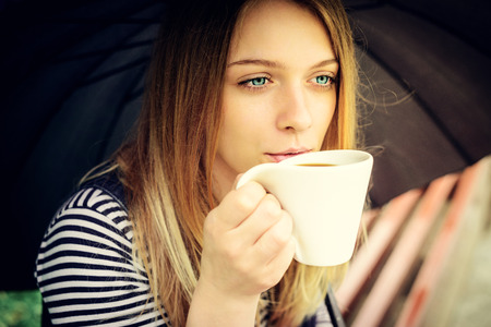 bad weather: womanl drinks fragrant coffee with pleasure under umbrella in bad weather Stock Photo