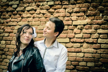 unusual wedding couple near a brick wall outdoors photo