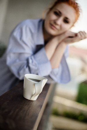 young beautiful woman early in morning with cup of coffee outdoors photo