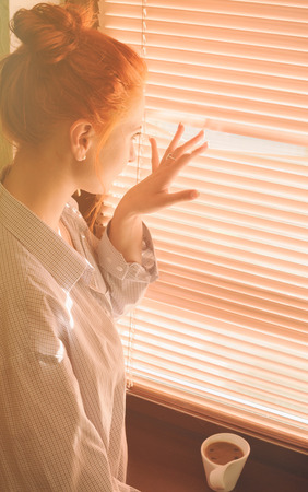 young beautiful woman early in morning with cup of coffee at window photo
