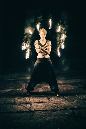fire show: active European girls carries out tricks for fire show at night