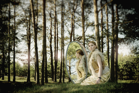 concept of wonderful fairy tale with beautiful girl in country of mirror photo