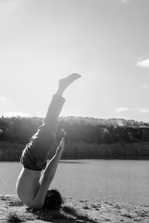 asanas: man practices asanas on yoga in harmony in black and white