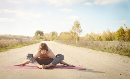 asanas: man practices asanas on yoga in harmony with the nature