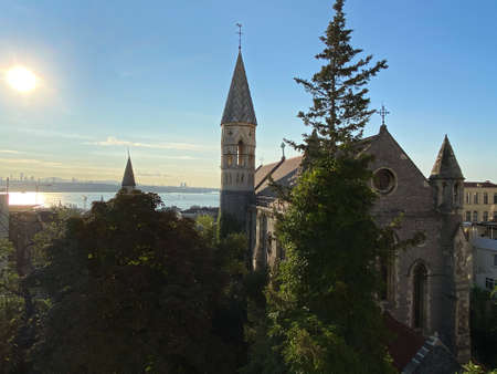 Old vintage medievel stone church building surrounded with trees. Istanbul Bosphorus at the background and ships