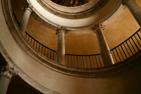 Spiral rounded ramp stairs. Into the dark, into the light. Rising up, going down Mystic lighting. Ancient historic walls and columns.