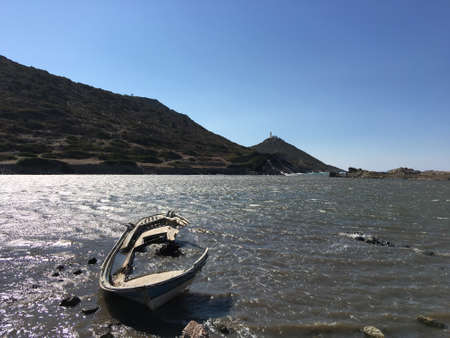 Wrecked boat on the Mediterranean sea water, mountains at the back and a lighthouse at the top of the hill. Sinking boat, end of the road.