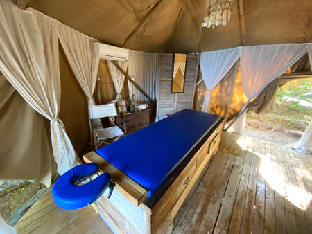 Blue comfortable massage bed in beige summer tent with white curtains and sea view open air. Relaxing exotic luxury summer holiday therapy outdoors. Banco de Imagens