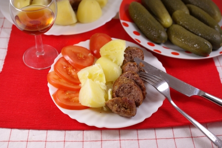 tasty steak on a plate with slices of tomatoes and potatoes  on the table photo
