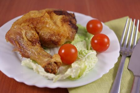 Roast chicken whole leg with tomatoes on table Stock Photo
