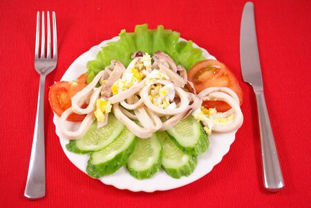 Squid salad and fresh vegetables on a plate on the table Stock Photo