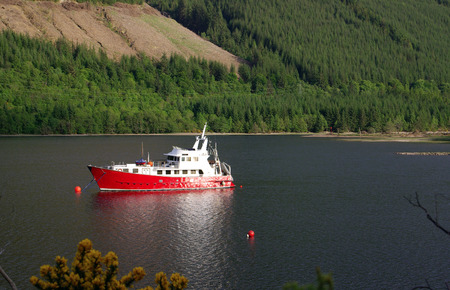 The red ship is in the harbor in Highland, Scotland photo