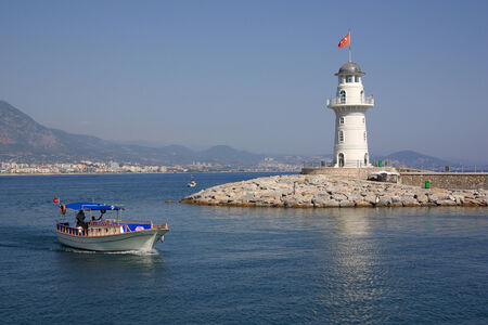 Lighthouse and boat in the port of Alanya, Turkey photo