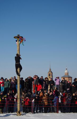 maslenitsa: SUZDAL, RUSSIA - February 21, 2015: Shrovetide in Russia. Man climbing the pole for prize during winter carnival Maslenitsa. Maslenitsa or Pancake Week is the ancient Slavic Holiday Editorial