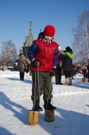 stilts: SUZDAL, RUSSIA - February 21, 2015: The boy is 8 years old on stilts on Shrovetide - the celebration and folk festival, Suzdal. Maslenitsa or Pancake Week is the ancient Slavic Holiday Editorial