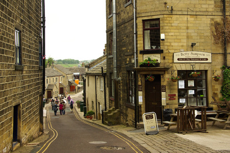 vibrant cottage: HAWORTH, ENGLAND - June, 2013: Old narrow street with tourists in the village of Haworth in summer day Editorial