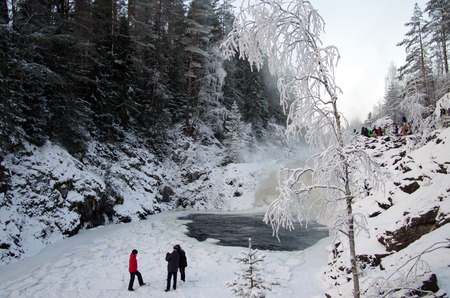 karelia: KARELIA, RUSSIA - January, 2016: People are photographed on the background waterfall Kivach in cloudy January day. Karelia, Russia Editorial