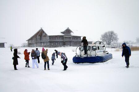 hovercraft: KARELIA, KIZHI, RUSSIA - January, 2016: Tourists photographed against the backdrop of a hovercraft