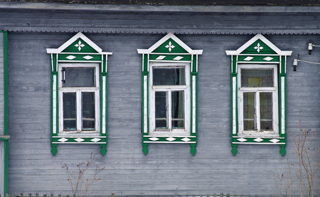 YAROSLAVL REGION, RUSSIA - MARCH, 2016: The facade of the old wooden houses with carved architraves