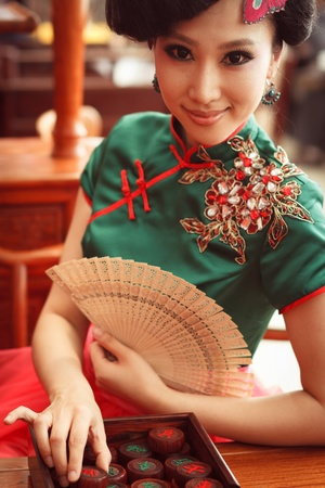 Woman wearing a cheongsam,Chinese classical costumes,In chess Stock Photo