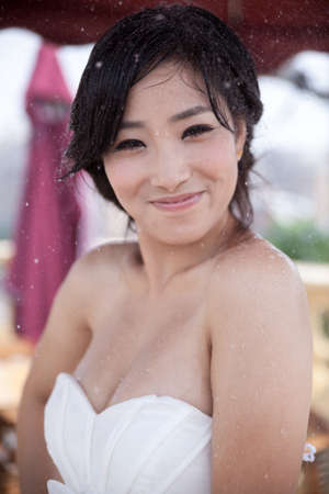 Asian girl, wearing a white dress standing in the rain Stock Photo