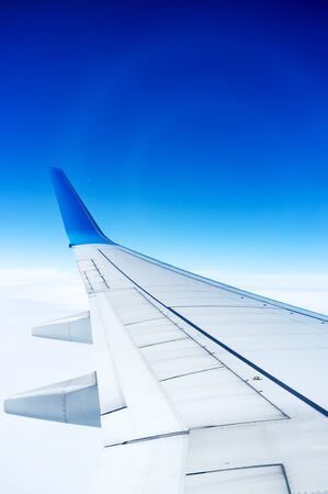 The planes wings, the background is blue sky, taken from the cabin Stock Photo