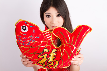 Chinese pretty girl wearing cheongsam holding chinese new year decoration Stock Photo