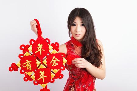 Chinese pretty girl wearing cheongsam holding chinese new year decoration Фото со стока