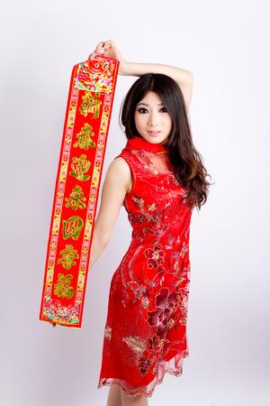 Chinese pretty girl wearing cheongsam holding couplets