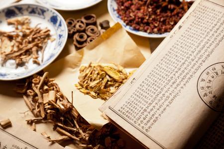 清朝では、テーブルの上の中国の漢方薬で古代中国の医療書籍します。 報道画像