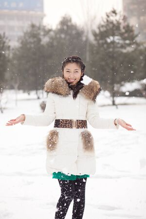 The Chinese girl playing in the snow