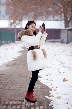 A pretty chinese girl taking photo in the park