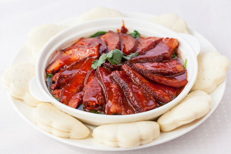 Chinese red-cooked pork belly on a white background