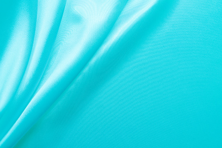 Smooth elegant wavy turquoise - pastel color silk or satin luxury cloth fabric texture, abstract background design.