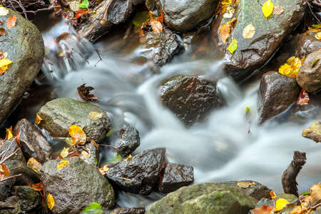 transient: Beautiful autumn creek with a little cascade. Stock Photo