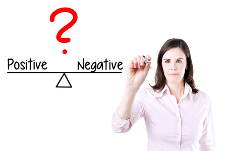 introspective: Young business woman writing on balance positive and negative Compare bar. Isolated on white. Stock Photo