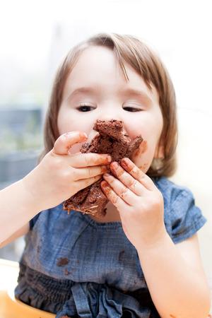Ein entzückendes kleines Mädchen genießen ihren Geburtstagskuchen.