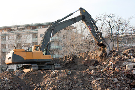 to thrash: Demolition truck in action. Demolition of an old block of flats.