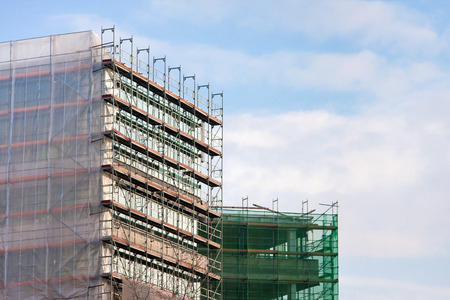 construction mesh: Staircase and scaffolding on a construction site, covered with mesh on sky background Stock Photo