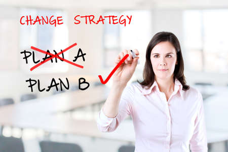 adapting: Young business woman writing Business plan strategy changing. Office background. Stock Photo