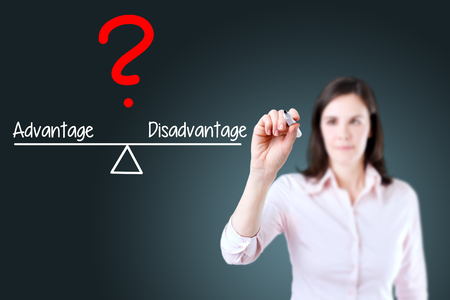 disadvantage: Young business woman writing Advantage and Disadvantage compare on balance bar. Blue background.