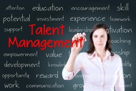 talent management: Business woman writing talent management concept. Blue background.