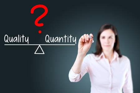 correlate: Young business woman writing quality and quantity compare on balance bar. Blue background. Stock Photo
