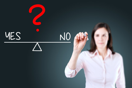 right vs wrong: Young business woman writing yes and no compare on balance bar. Blue background. Stock Photo
