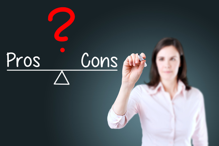 conform: Young business woman writing pros and cons compare on balance bar. Blue background.