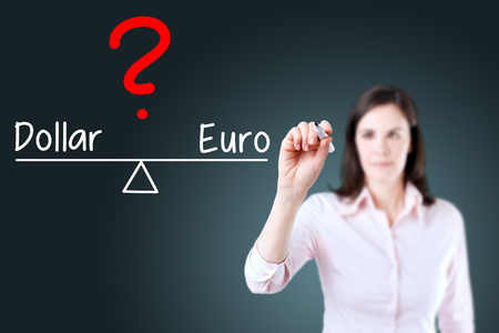 valorization: Young business woman writing dollar and euro compare on balance bar. Blue background.